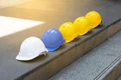 White yellow and blue hard safety helmet hat on concrete floor Royalty Free Stock Photography