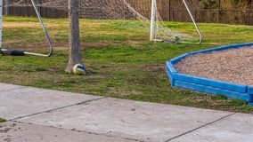 White, yellow and blue soccer ball resting on the ground at a park in the golden hour sun royalty free stock photo