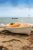 White and Yellow boat on shore. White and Yellow boat on sandy beach. Beach with washed up seaweed, sea horizon in background. Location Christchurch, Dorset UK Stock Images