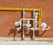 Outdoor Gas Line Regulators Pipes. White and yellow gas lines, pipes, regulators against a red brick wall stock photography