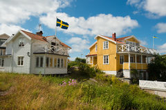 White and yellow houses. A white and a yellow house with Swedish banner in Swedish westcoast stock images