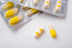 White and Yellow Medication Capsules. White and yellow medicine  capsules from silver packaging on a white surface Stock Photos