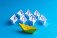 White and yellow paper boat or ship in one direction on blue background royalty free stock image