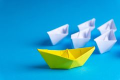 White and yellow paper boat or ship in one direction on blue background royalty free stock photography