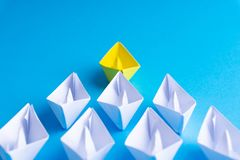 White and yellow paper boat or ship in one direction on blue background stock images