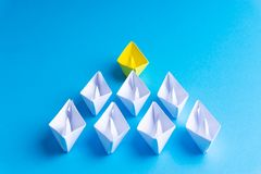 White and yellow paper boat or ship in one direction on blue background royalty free stock photo