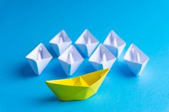 White and yellow paper boat or ship in one direction on blue background stock image