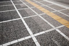 White and yellow road marking lines on gray cobblestone Royalty Free Stock Images