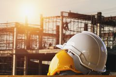 White and yellow safety helmet in construction site. With sunset royalty free stock photo