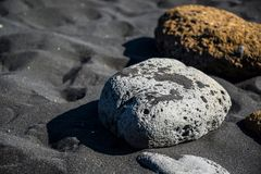 White and yellow stones on the black sand on the beach of a town Vik in Iceland stock photos