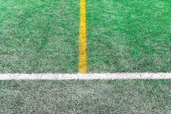 White and yellow stripes on the artificial green soccer field.  Stock Photography