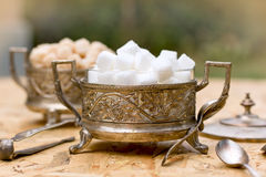 White and yellow sugar (cubes) in silver containers - antique bowls Royalty Free Stock Images