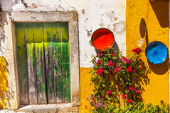 White Yellow Wall Green Door Mediieval City Obidos Portugal. White Yellow Wall Green Door Orange Blue Bowls Red Roses Street 11th Century Medieval Town Obidos Stock Photo
