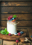 White yogurt with fresh berries, peach and mint leaves Stock Image