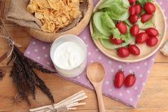 White yogurt and fresh cherry tomatoes with cornflake. Royalty Free Stock Images