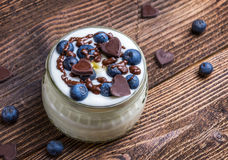 White yogurt in glass bowl with whole blueberries and chocolate on wooden rustic table. Closeup detail. Stock Photo