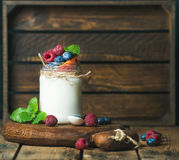White yogurt in jar with fresh berries, peach, mint leaves Royalty Free Stock Photo
