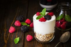 White yogurt with muesli and raspberries in glass bowl on rustic. White yogurt with muesli, blackberries and raspberries in glass bowl on rustic wooden Stock Photo