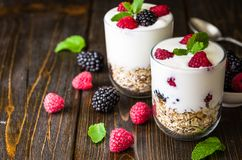 White yogurt with muesli and raspberries in glass bowl on rustic wooden background. White yogurt with muesli and raspberries in glass bowls on rustic wooden Royalty Free Stock Photography