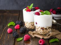 White yogurt with muesli and raspberries in glass bowl on rustic wooden background. White yogurt with muesli and raspberries in glass bowls on rustic wooden Royalty Free Stock Image