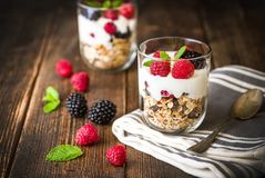 White yogurt with muesli and raspberries in glass bowls on rustic wooden background. White yogurt with muesli and raspberries in glass bowls on rustic wooden Stock Images