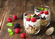 White yogurt with muesli and raspberries in glass bowls on rustic wooden background. White yogurt with muesli and raspberries in glass bowls on rustic wooden Royalty Free Stock Images