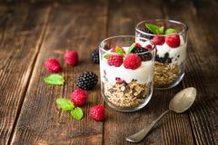 White yogurt with muesli and raspberries in glass bowls on rustic wooden background. White yogurt with muesli and raspberries in glass bowls on rustic wooden Stock Image
