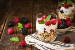 White yogurt with muesli and raspberries in glass bowls on rusti. C wooden background Royalty Free Stock Photos