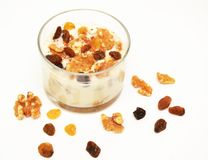White yogurt with nuts and raisin on white background. Healthy breakfast stock photo