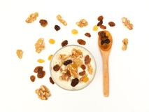 White yogurt with nuts and raisin on white background. Top view. Healthy breakfast stock image