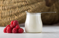 White yogurt with raspberries in glass bowl on white table with. Spoon on the top Royalty Free Stock Image