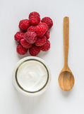 White yogurt with raspberries in glass bowl on white table. Top. View Royalty Free Stock Images