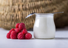White yogurt with raspberries in glass bowl on white table. White yogurt with raspberries in glass bowl wth spoon on white table Royalty Free Stock Image