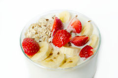 White yogurt with strawberry, banana, oat flakes, flax seeds on a white background sprinkled with flax seeds Royalty Free Stock Images