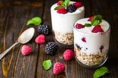 White yogurt with muesli and raspberries in glass bowl on rustic wooden background. White yogurts with muesli and raspberries in glass bowl on rustic wooden Royalty Free Stock Photos