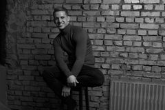 White young guy sitting on a chair and smilling near a gray brick wall, black-and-white photo. Casual man sitting on a chair near a gray brick wall, black-and royalty free stock photography