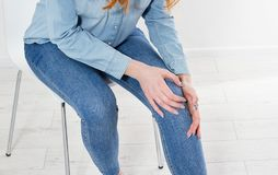 White of young woman massaging her painful knee, Medical and health care concept. Copy space stock images
