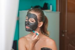 White young woman wearing a face mask at home on a turquoise background. European woman in black mask for the face close up and c royalty free stock photos