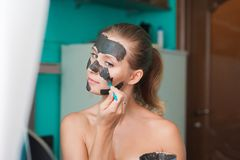 White young woman wearing a face mask at home on a turquoise background. European woman in black mask for the face close up and c stock images
