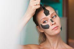 White young woman wearing a face mask at home on a turquoise background. European woman in black mask for the face close up and c stock photography