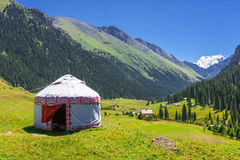 White Yurt in the mountains of Kyrgyzstan. Beautiful mountain landscape with the white Yurt, decorated with a red ornament, Kyrgyzstan Stock Photos