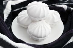 White zephyr marshmallow on plate with warm scarf around Stock Photos