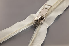White zipper. Studio photography of white zipper opened on a half to a gray surface Royalty Free Stock Image
