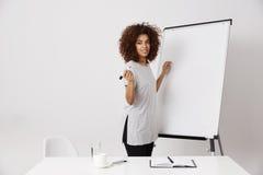 Whiteboard cercano derecho sonriente del marcador de la empresaria africana en la oficina expnaining un nuevo concepto de lanzami Foto de archivo libre de regalías