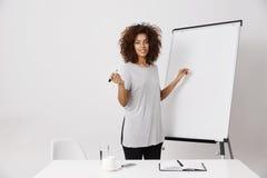 Whiteboard cercano derecho sonriente del marcador de la empresaria africana en oficina Imagen de archivo libre de regalías