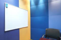 Whiteboard contra la pared azul Foto de archivo libre de regalías