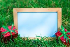 Whiteboard en blanco para su texto en fondo del césped Foto de archivo libre de regalías