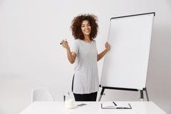 Whiteboard seco en blanco cercano derecho sonriente de la señora africana del negocio en el espacio abierto de la oficina, explic Fotografía de archivo libre de regalías