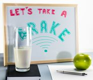 A whiteboard titled `Let`s take a brake` with red and green letters, cup of milk and a green apple. A glass of milk is placed on top of a black book. There is stock image