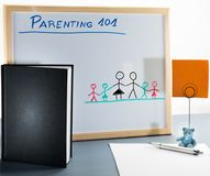 A whiteboard used for parenting classes and sex education in highschool or university. Room for copy, black book cover, white sheet of paper, silver pen, blue Royalty Free Stock Image